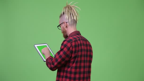 Back view of bearded hipster man with dreadlocks using digital tablet