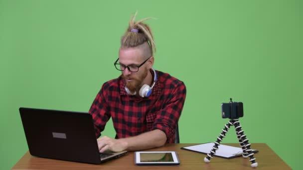 Hezký vousatý bokovky muž vlogging proti dřevěný stůl