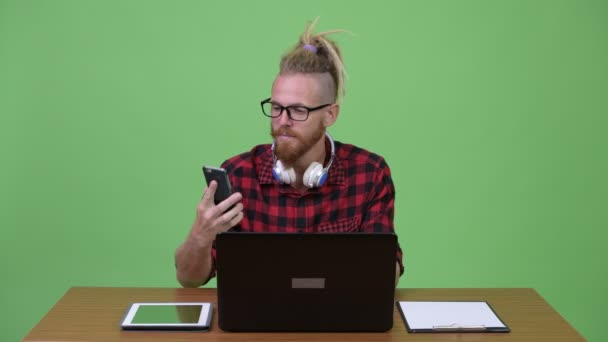 Happy bearded hipster man video calling with phone while working against wooden table