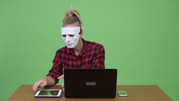 Bokovky muž nosí masku jako hackerů a multi-tasking práce proti dřevěný stůl