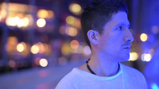 Hispanischer Mann denkt bei Nacht gegen den Blick auf die Stadt