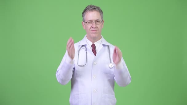 Portrait of mature man doctor covering ears as three wise monkeys concept