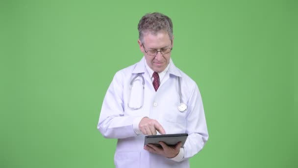 Portrait of mature man doctor thinking while digital tablet