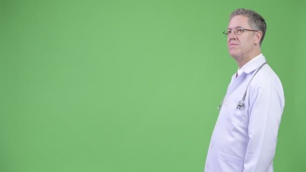 Profile view of mature man doctor wearing eyeglasses