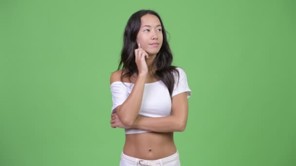 Young happy beautiful multi-ethnic woman thinking