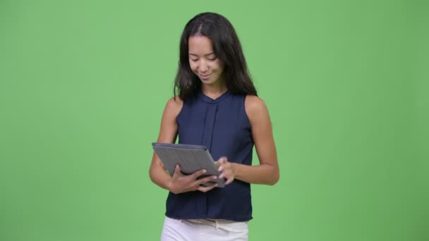 Young happy pregnant multi-ethnic businesswoman using digital tablet