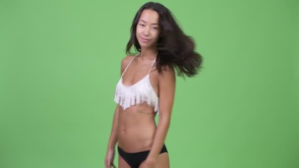 Rear view of young beautiful multi-ethnic woman wearing bikini ready for vacation