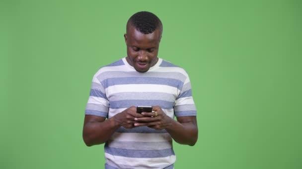 Šťastný afrického mladíka s úsměvem při používání telefonu