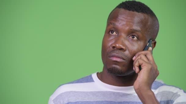 Boldog afrikai fiatalember beszél a telefonon