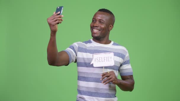 Young happy African man taking selfie with paper sign