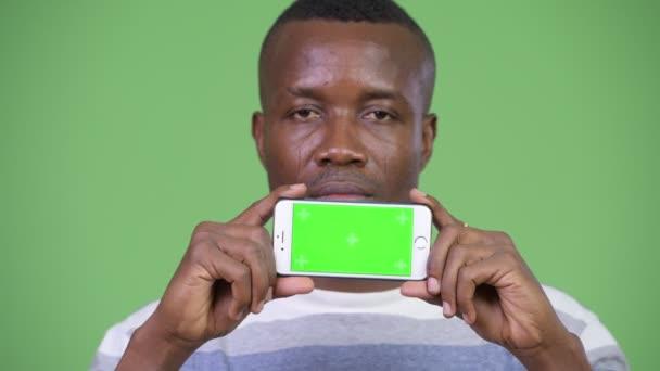 Boldog afrikai fiatalember arra gondolt, miközben bemutatja a telefon