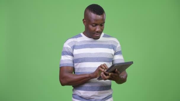 Happy afrického mladíka pomocí digitálních tabletu
