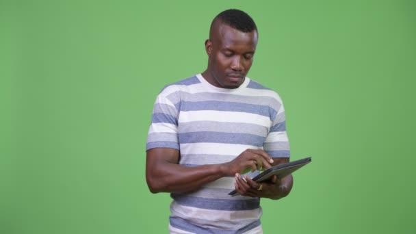 Mladí africké muž myšlení při používání digitálních tablet