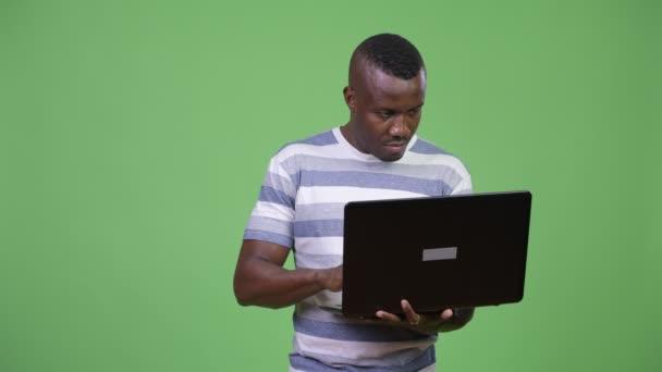 Mladí africké muž myšlení při používání notebooku
