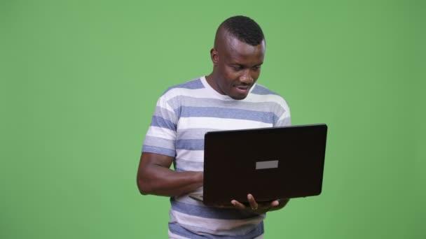 Happy afrického mladíka myšlení při používání notebooku