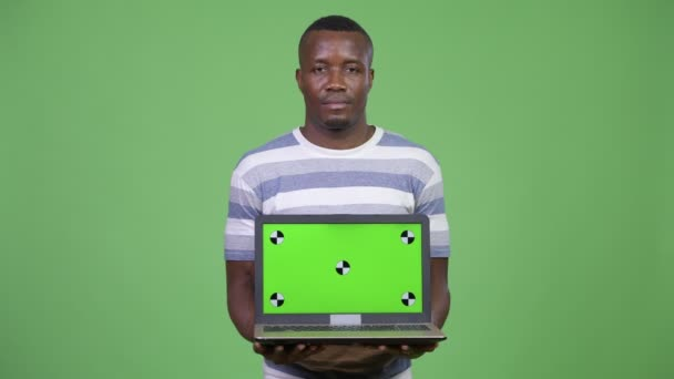 Young happy African man showing laptop