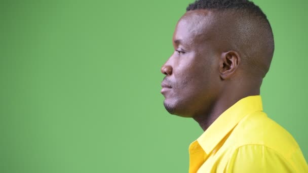 Profile view of young African businessman thinking while wearing yellow shirt