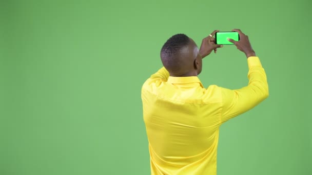 Rear view of young African businessman wearing yellow shirt taking picture with phone