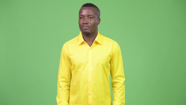 Young African businessman thinking while wearing yellow shirt