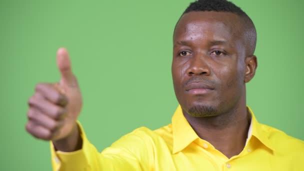 Mladý šťastný africký podnikatel myšlení zároveň dává palec