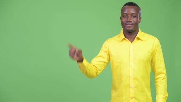 Felfelé mutató fiatal boldog afrikai üzletember