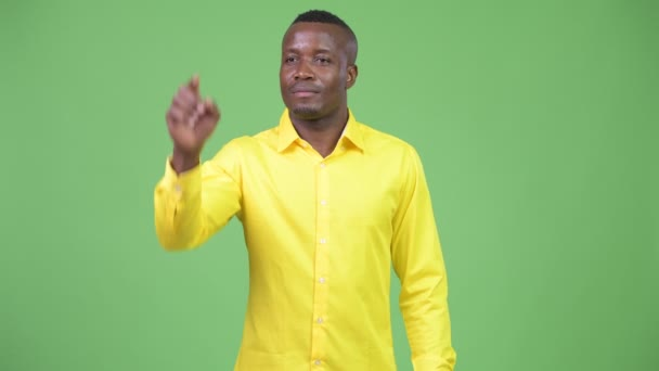 Young happy African businessman pointing finger
