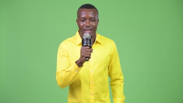 Mladý šťastný africký podnikatel prezentovat něco s mikrofonem