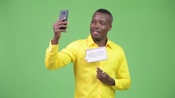 Young happy African businessman taking selfie with paper sign