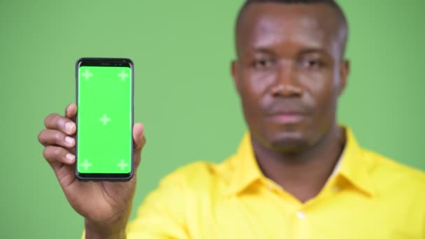 Young happy African businessman showing phone