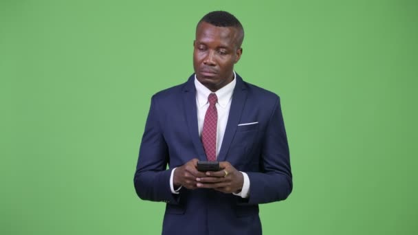 Young African businessman thinking while using phone