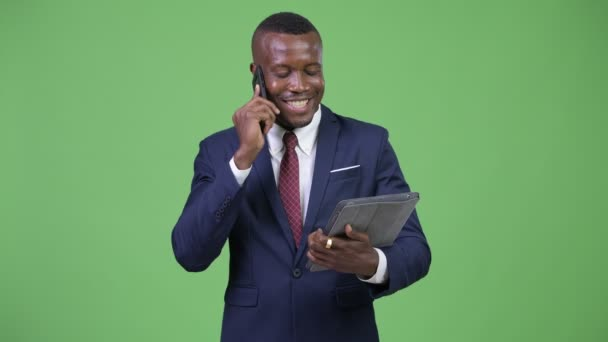 Young happy African businessman talking on the phone while using digital tablet