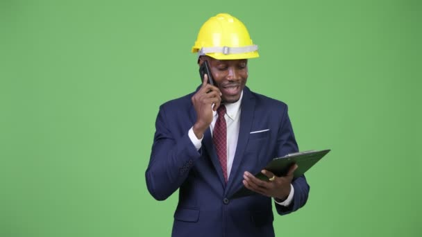 Young happy African businessman as engineer talking on the phone while reading on clipboard