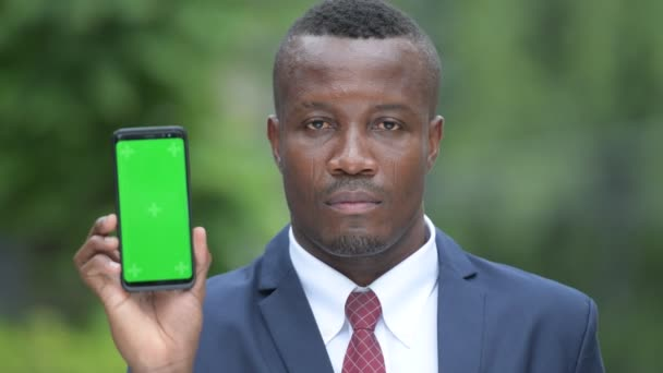 Young happy African businessman showing phone outdoors