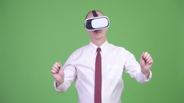 Reifer glatzköpfiger Geschäftsmann mit Virtual-Reality-Headset