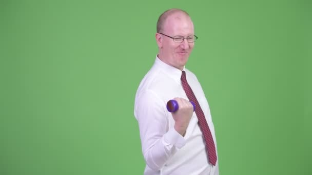 Studio shot of mature bald businessman wearing eyeglasses against chroma key with green background