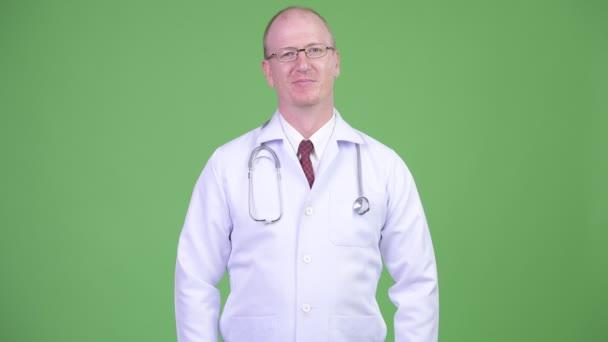 Doktor šťastný starší plešatý muž nosí brýle proti zeleným pozadím
