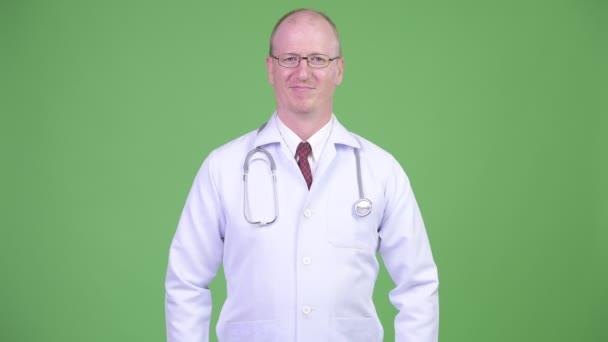 glücklich reifer glatzköpfiger Arzt mit verschränkten Armen vor grünem Hintergrund