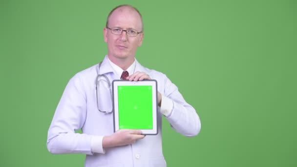 Šťastný starší plešatý muž lékař zobrazeno digitální tablet