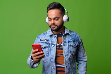Young bearded Indian man against green background