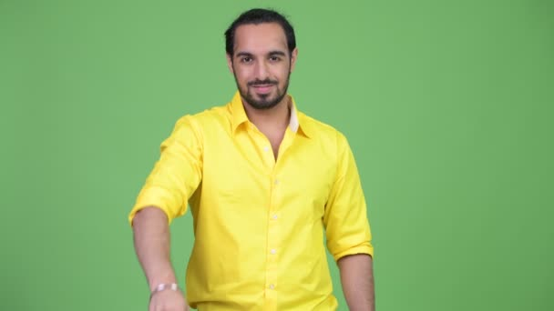 Young happy bearded Indian businessman pointing to camera