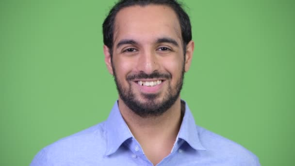 Young happy bearded Indian businessman smiling