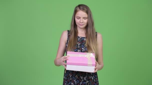 Mladá krásná těhotná žena hledá překvapen při otevírání krabičky
