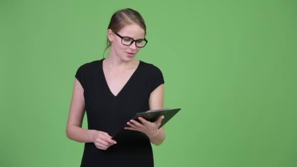Young beautiful businesswoman with eyeglasses talking while holding clipboard