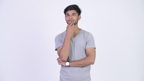 Mladý šťastný indické vousáč usmívající se přitom myšlení