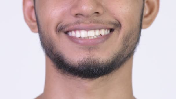 Smile of young happy bearded Indian man