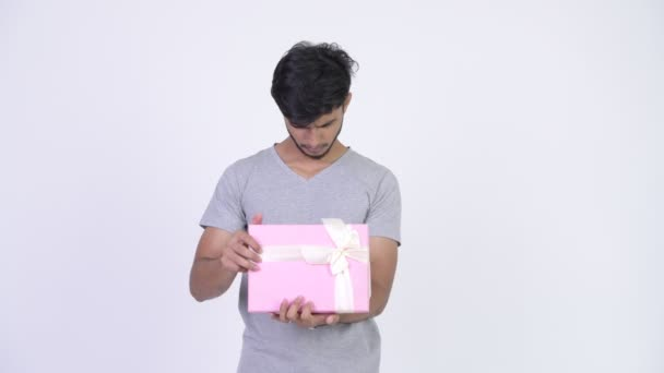 junge glückliche bärtige indische Mann öffnet Geschenkbox und schaut überrascht