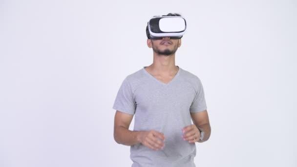 junger schöner bärtiger indischer Mann mit Virtual-Reality-Headset