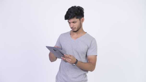 Young happy bearded Indian man thinking while using digital tablet