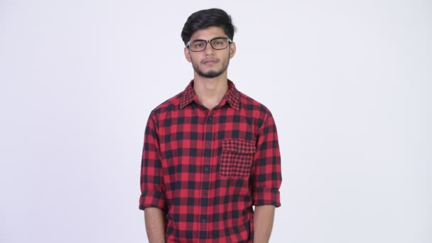 Young handsome bearded Indian hipster man wearing eyeglasses