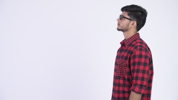 Profile view of young handsome bearded Indian hipster man